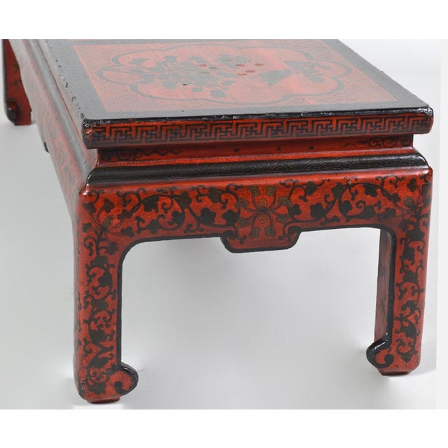 A rare and incredibly beautiful high quality vintage red Chinoiserie coffee table. Designed with a central landscape scene...