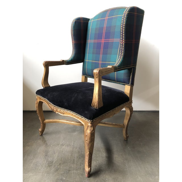 A lightly distressed gilt wood frame with carved detailing; plaid-patterned upholstery on the seat back and a dark velvet...
