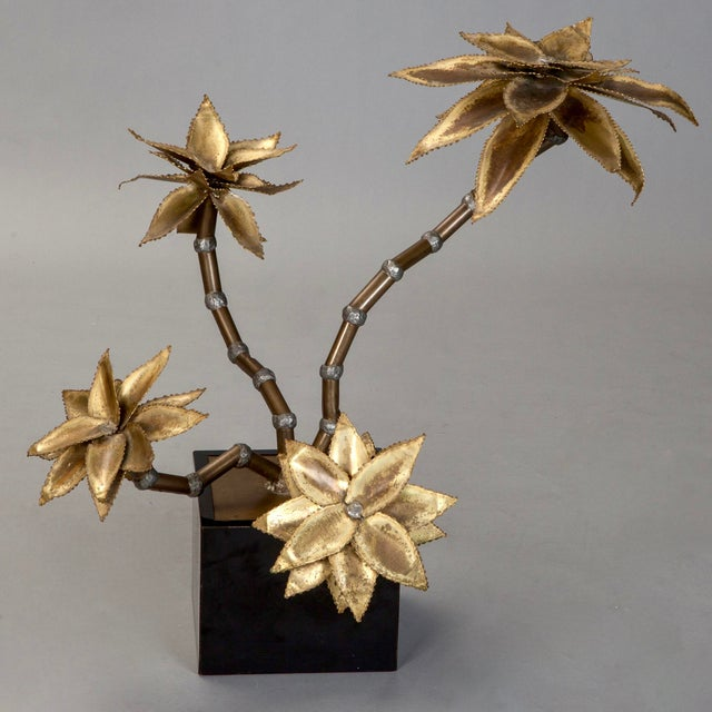 Dramatic circa late 1960s floral sculpture mounted on black wood box and has four bamboo-like stems with four large brass...