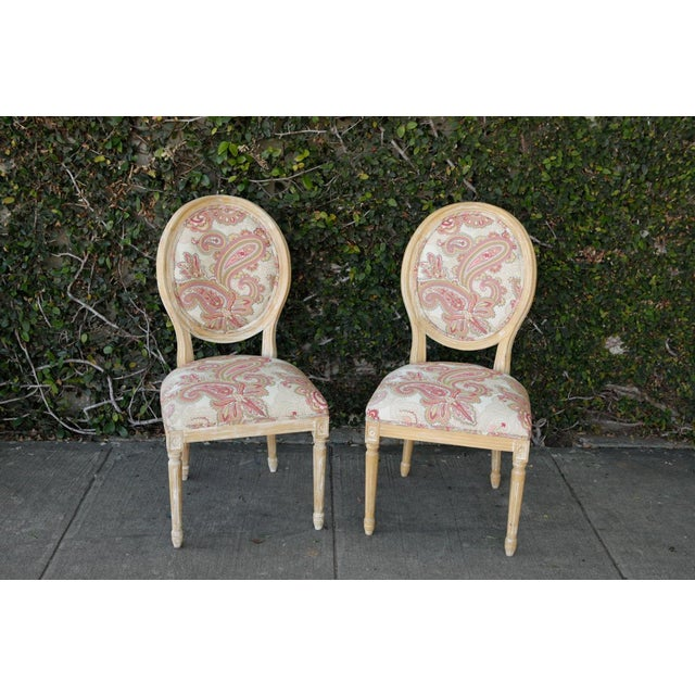 Pair of Louis side chairs with newly upholstered fabric in a colorful paisley fabric. White washed light wood base/frame....