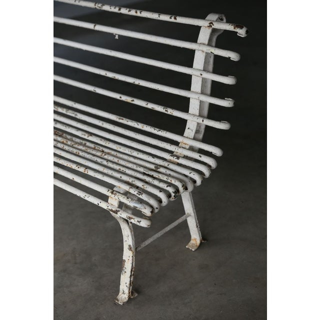 Long French iron bench in early white paint. Excellent example of early 20th century quality French wrought-iron. In...