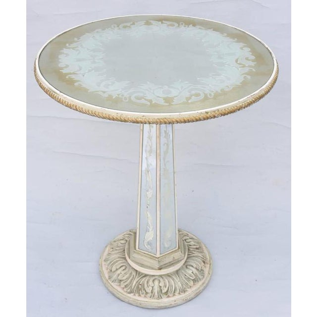 Occasional table, having a painted finish with natural wear, its round, églomisé, mirrored top, with a scrolling,...