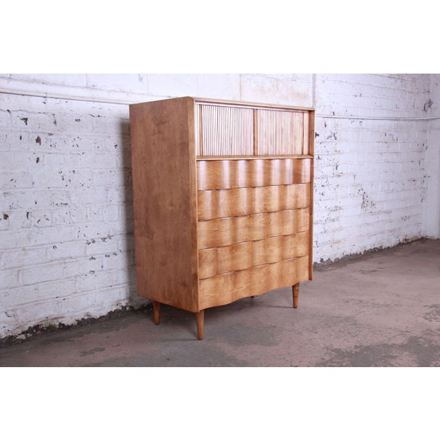 Offering a rare and exceptional mid-century modern wave front highboy dresser designed by Edmond Spence. The dresser...