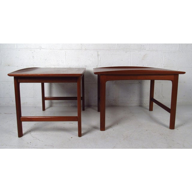 Two vintage-modern end tables made in Sweden, features sculpted legs, beveled top and attractive teak wood grain...