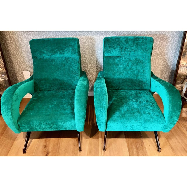 A pair of stylish Italian midcentury armchairs, circa 1950s in a deep green velvet upholstery. Blackened metal legs with...