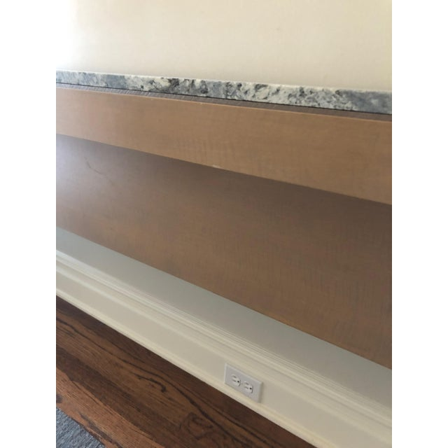 An extremely long custom contemporary console table having a light wood base with simple clean lines and a sleek grey and...