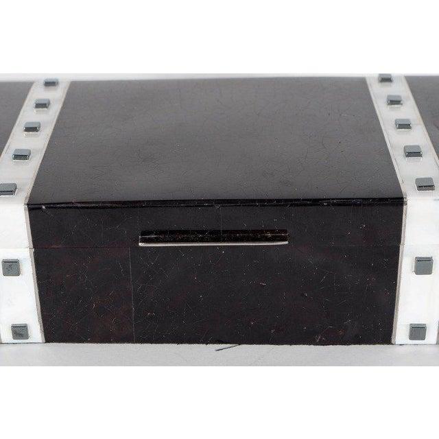 This exquisite black lacquer box features a recurring square art deco motif in lustrous hematite, two pearlescent kabibi...
