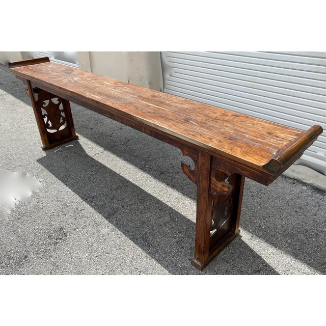 Chinese console table with hand carved spandrels on both side of the table. A long elmwood altar or console table features...