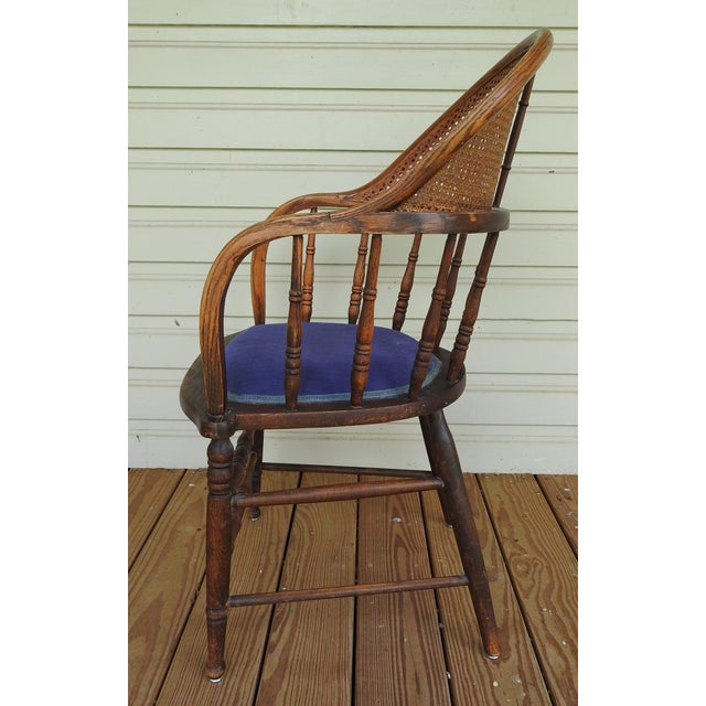 Refinished circa 1915 oak bow back arm chair with cane back. The seat cane has been replace with webbing and blue fabric....