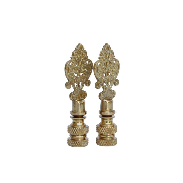 A pair of small fancy brass lamp finials. Fits a standard size lamp harp. Measurements per finial.