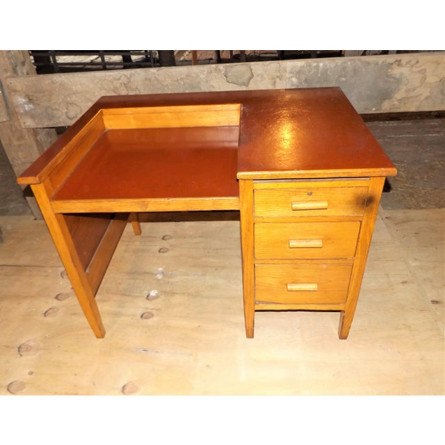 Here is an unusual old oak desk with a maroon top. Top is maybe made of fiber. It's kind of unusual, the writing area is...