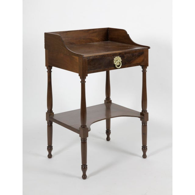 An antique American Federal mahogany table, with a shaped gallery on three sides of the top, one drawer, and a shelf...