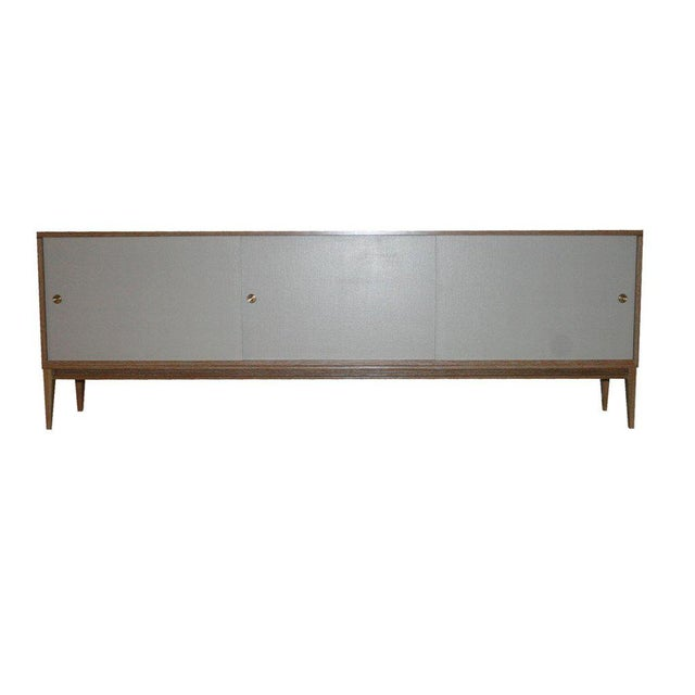 Cerused Oak sliding linen door console on taped legs detailed with apron surround. White oak construction with natural...