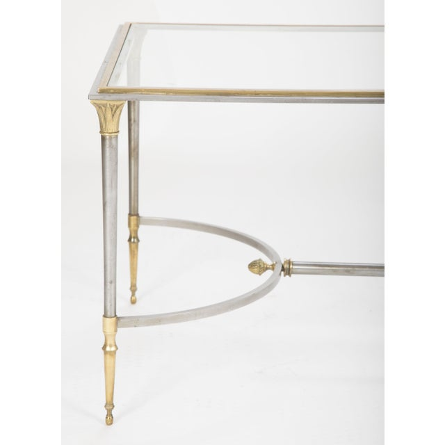 An elegant French steel and bronze glass top coffee/cocktail table with gun metal patina by Maison Charles.