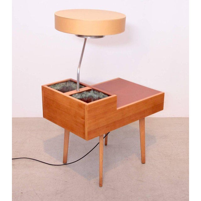 A chairside table with lamp and planters by George Nelson for Herman Miller. The tabletop is wrapped in leather of a...