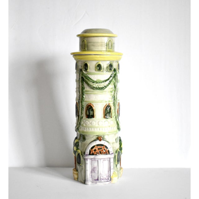 A vintage tall, ceramic, cylindrical pasta container in the trompe l'oeil form of a castle tower, with green garlands...