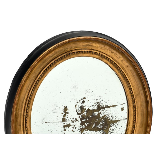 Louis XVI period French oval mirror featuring hand-carved wood frame molded with beading. The central mirror is an oval...