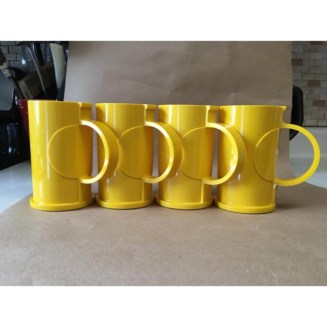 Enjoy a brilliant pop of color with these cheery lemon yellow mugs by Gunnar Cyren for Dansk Designs.