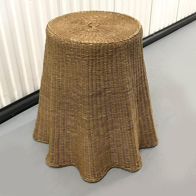 Elegant woven wicker table with drape-effect styling, circa late 1970s. Wire-frame armature on underside holds the shape...