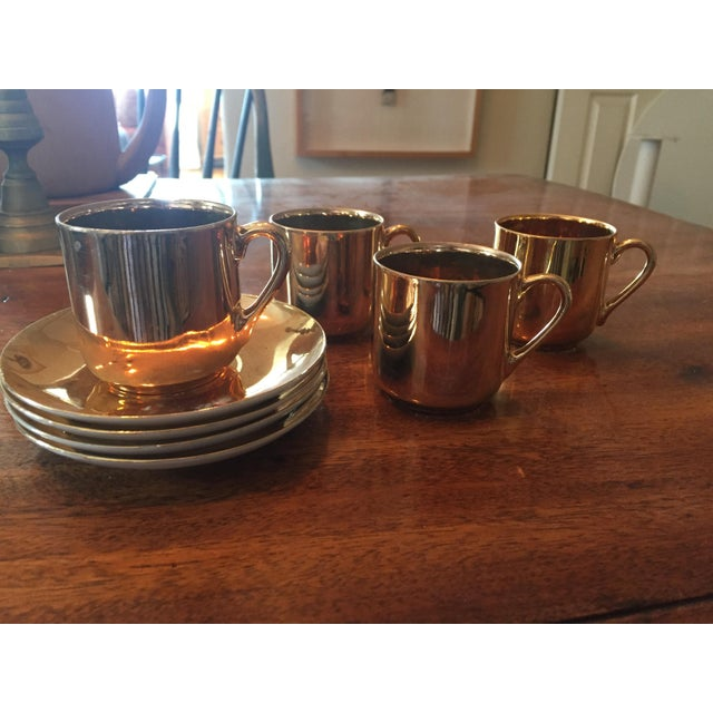 Vintage set of four small cups and saucers from Japan in a copper finish.
