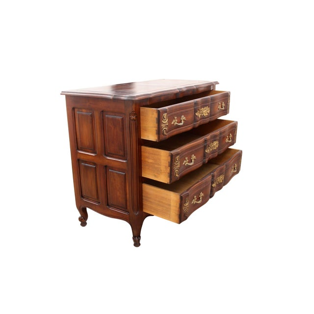 French provincial dresser with carvings and brushed gold detailing. The case is wood construction and houses three...