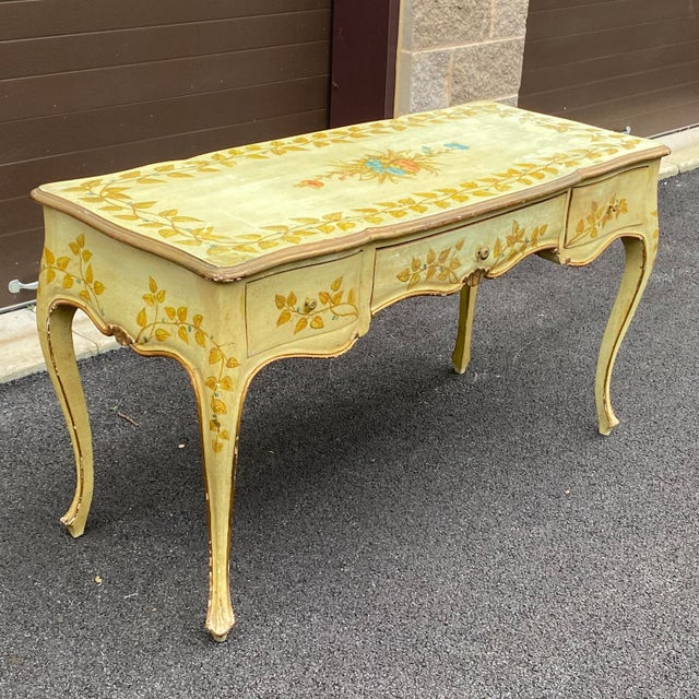 A charming three drawer desk on cabriole legs finished on all sides with original painted finish that has distressed over...