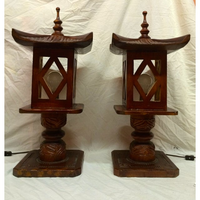A stunning pair of hand-carved wooden pagoda lamps. The lamps have their original wiring, wired for U.S. use and are in...