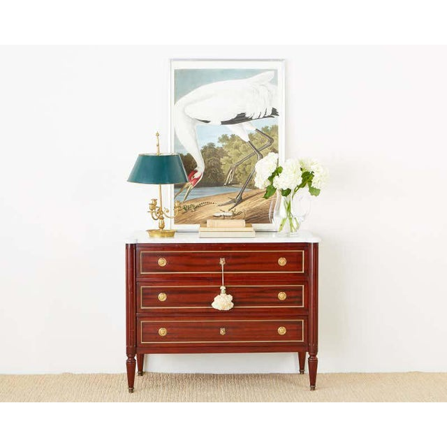Fine French mahogany commode, chest of drawers, or dresser featuring a dramatic conforming Carrara marble top. The...
