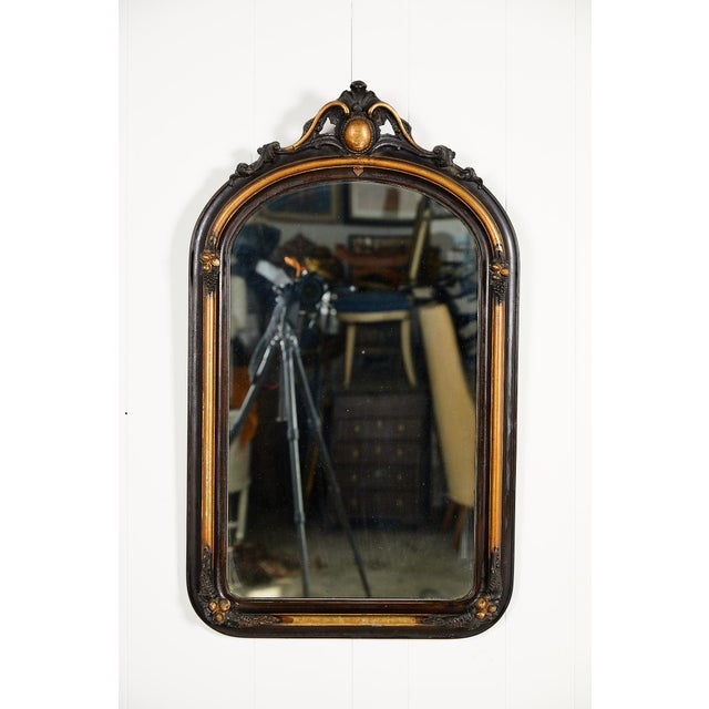 Early 20th Century French ebonized and gilded wall mirror in the Louis Philippe style with a domed crown and oak leaf...