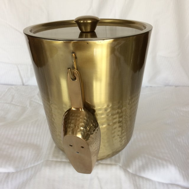 Gold anodized stainless steel insulated ice bucket with hanging scoop. Scoop measures 6 1/2 inches long and 2 1/4 inches...