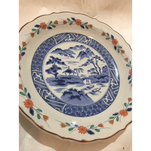 A beautiful Japanese Porcelain Plate with wonderful scenery in the center and floral decorations all around. A great...