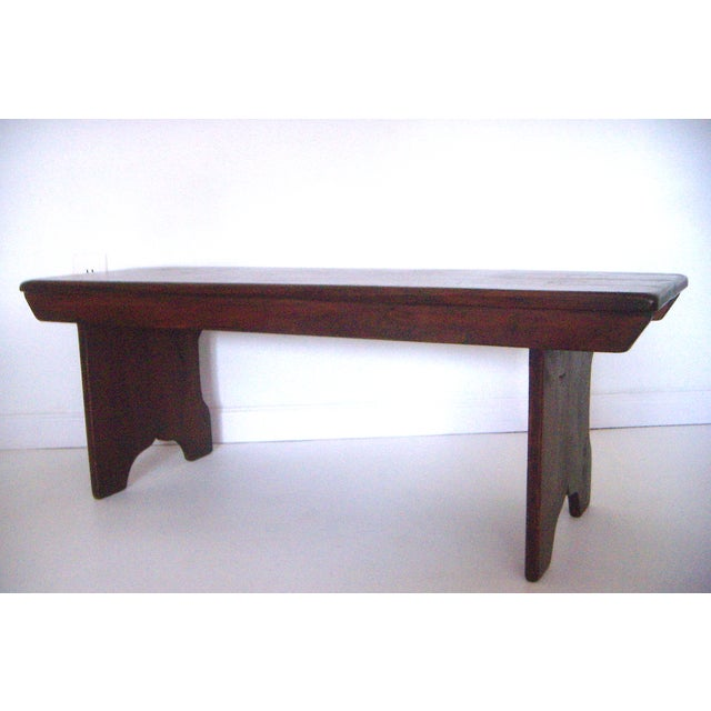 Useful solid pine bench that is stained a rich warm brown shade, and refinished by East2West Furniture. Two ogee style...