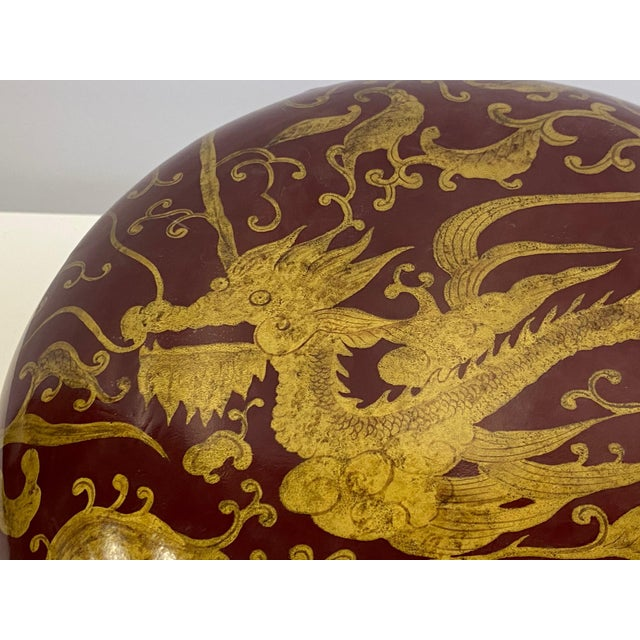 Gorgeous round jewel of a red laquered lidded box having gold Asian inspired decoration with dragons and birds.