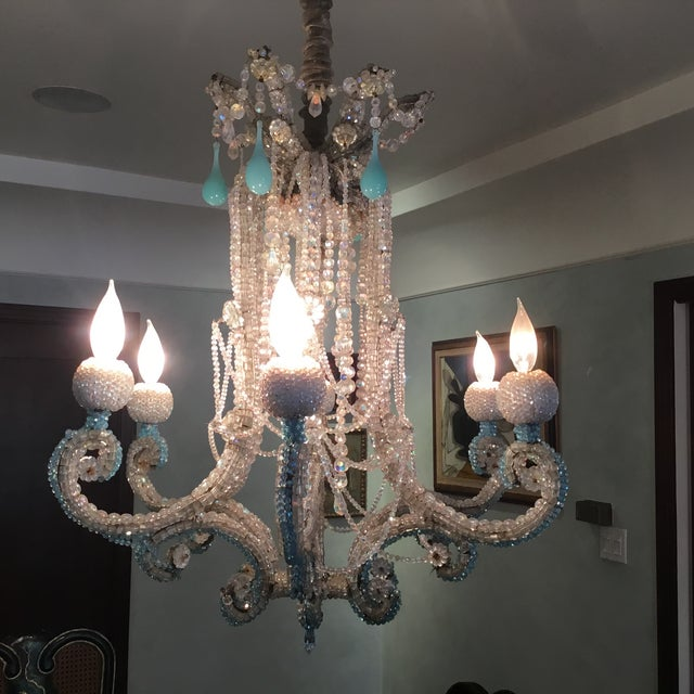 Gorgeous crystal chandelier with six arms. This piece is covered in clear and turquoise blue crystals. Stunning and ornate!