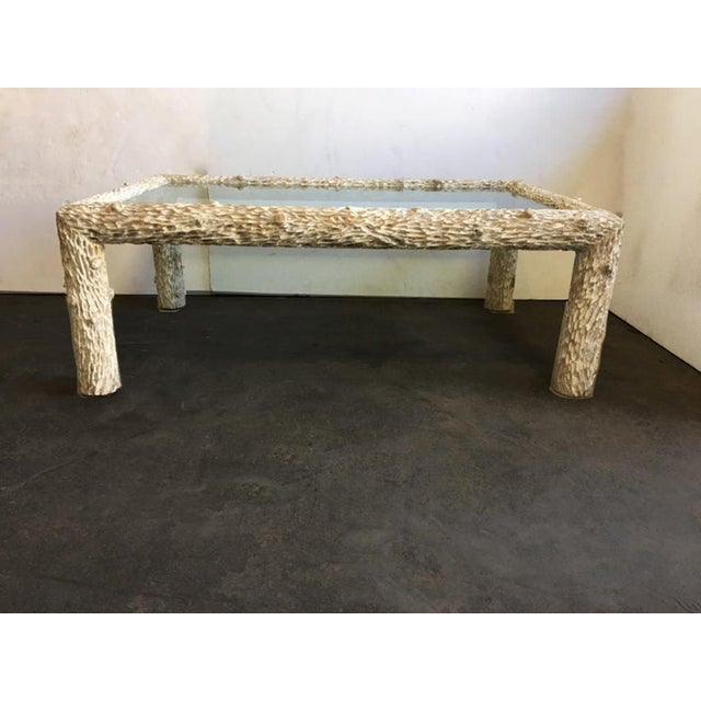 An organic glass top coffee table with a whitewashed finish sculpted wood trunk frame.
