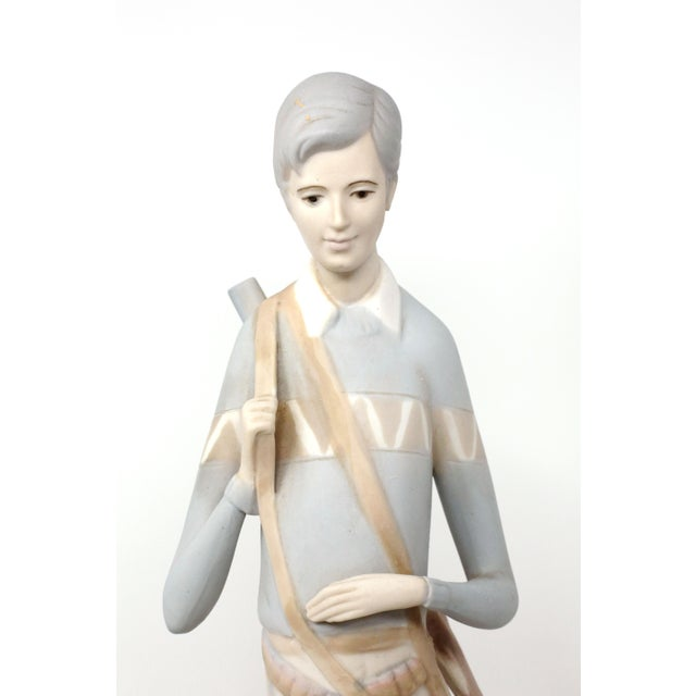 A tall ceramic figure of a hunter with shotgun, ducks, and dog. Gorgeous blush color with periwinkle accents. Made by...