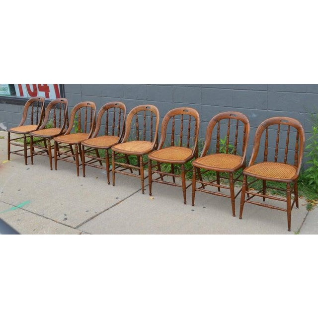 Dining room chairs, set of 8, with caned seats. Antique Windsor bow-back style in soft pine finish with cut-out handles....