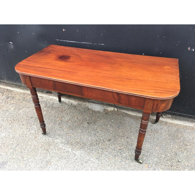 Incredible (circa 1850's) English antique writing desk. Amazing figured solid walnut top has been lovingly restored and...