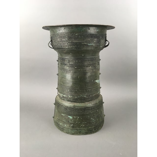 Antique Southeast Asian patinated bronze rain drum side table with heavily detailed textured pattern and handles....