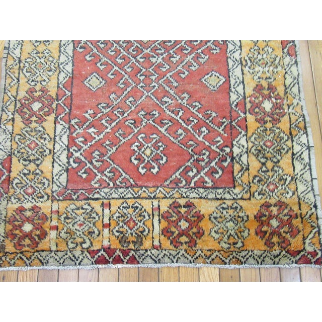 This is a small hand-knotted vintage Turkish Anatolian rug. It is made with wool dyed in primary colours. The rug has a...