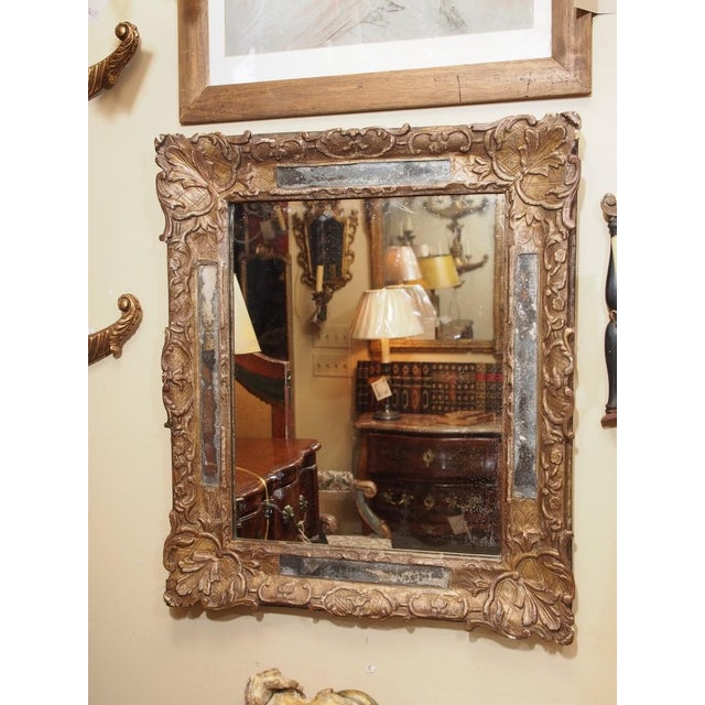 Carved wood and gilded mirror with original silvered slip glass border. Large mirror was replaced. Shell, flower and leaf...