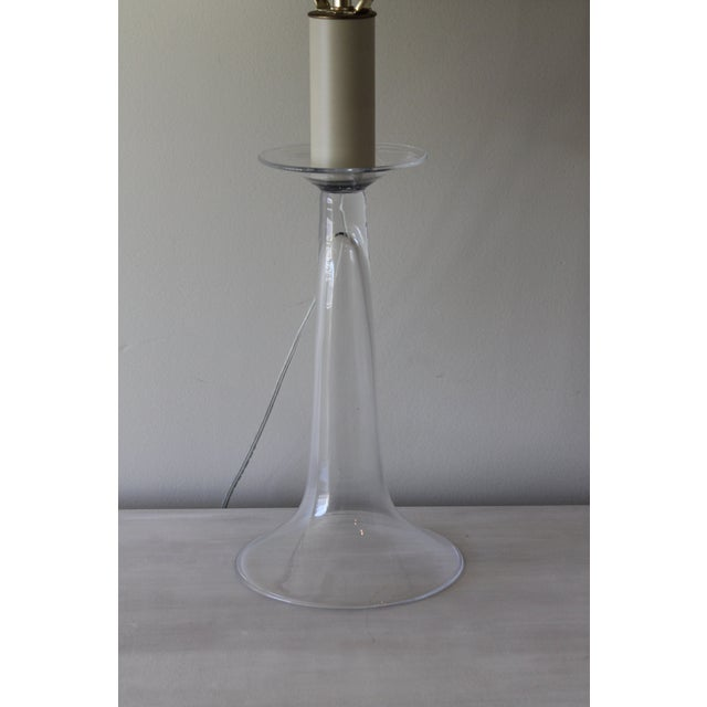 This classic glass table lamp is made of mouth blown glass. The lamp base stands with simplified elegance and the raw silk...