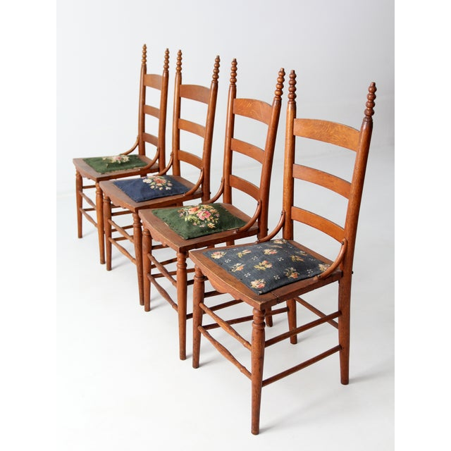 A set of four Victorian era needlepoint chairs. The wood frame ladder back chairs feature decorative needlepoint...