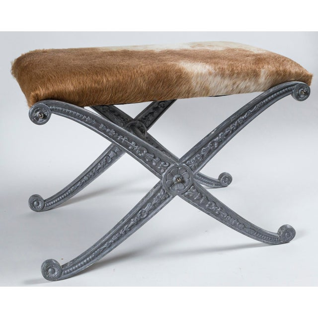 Pair of Neoclassic X-frame upholstered benches, 20th century. Metal frames with matte silver finish and impressed floral...