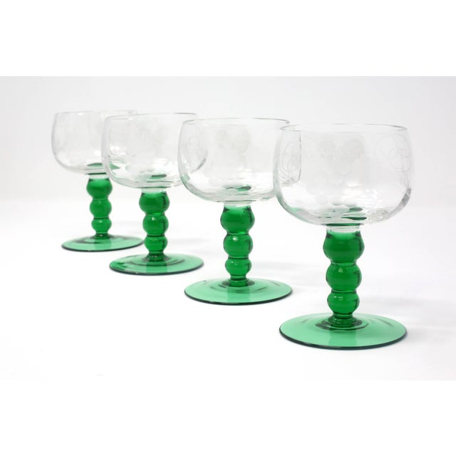 A set of four mid-century cordial glasses, with an etched grapes and leaves design, and green glass stems. Excellent...