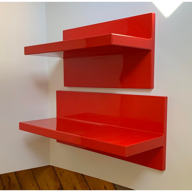 A pair of red plastic wall-hung shelves made by Kartell. The shelves are different lengths, but reversible as to whether...