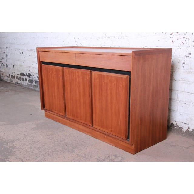 A gorgeous mid-century modern walnut sideboard or credenza designed by Merton Gershun for Dillingham. The credenza...