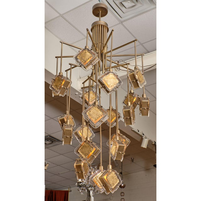 Murano glass gold and bronze chandelier with multiple arms holding bronze boxes with 23 carat gold leafed clear glass. We...