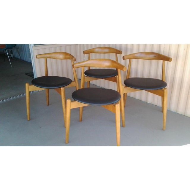 set of 4 elbow chairs in excellent condition with black vinyl seats. not sure how old chairs are
