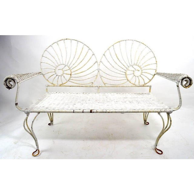 Wicker wrapped Iron loveseat bench with Nautilus Shell motif back. Stylish form, solid and ready to use, wicker shows...